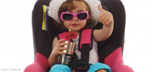 Kind mit Getränk und Sonnenbrille im Kindersitz